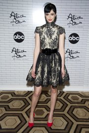 Actress Krysten Ritter wears a lace dress, which is a fine choice for a summer wedding.