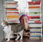 Allie Alvis, a Kansas University student studying linguistics, won the Snyder Book Collection Contest this year for her extensive collection of books about language and an essay on the subject. Alivs is pictured with some of her books and her cat Tiny.