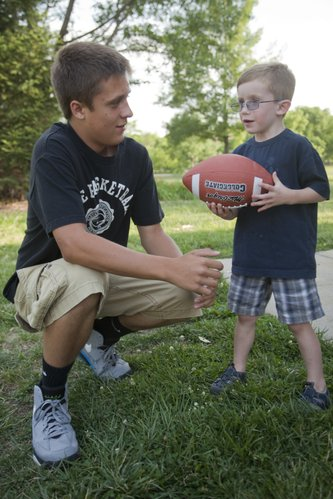 Dallas Hunt, 14, works with Cooper Keffer, 4, on how to throw a spiral pass. The two Lawrence residents have become like brothers after Dallas researched Cooper's Cause Foundation and choose to donate $300 he found in a parking lot to the foundation which helps families with pediatric heart patients like Cooper. Dallas raised additional money for the foundation by collecting donations in his school and neighborhood.