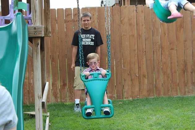 Dallas Hunt, 14, gives Cooper Keefer a push on the swings Sunday, June 3, 2012, at Cooper's home in Lawrence.  The two Lawrence residents have become like brothers after Dallas researched Cooper's Cause Foundation and choose to donate $300 he found in a parking lot to the foundation which helps families with pediatric heart patients like Cooper.