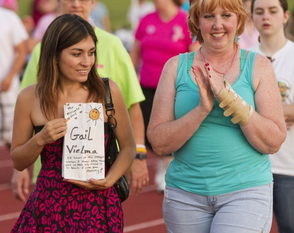 Ashley Conway, left, carries a luminary honoring her mother, Gail Vielma, as she walks with Dana Conway during the 2012 Relay for Life of Douglas County event.