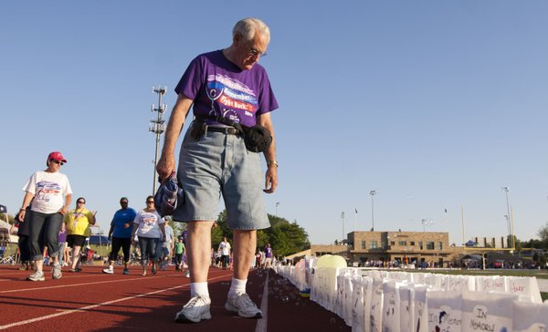 Forty-three-year cancer survivor Gary Watson, Lawrence, looks at the luminaria lining the track as he participates in the Relay for Life of Douglas County event held Friday, June 8, 2012, at the Free State High School track.