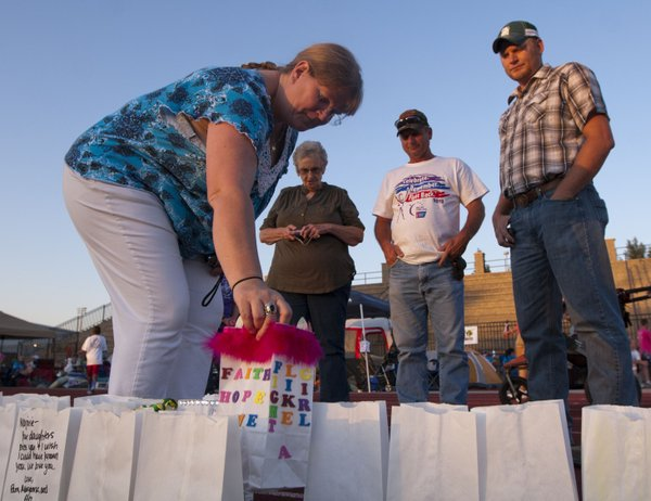 Susan Harrison places a luminary along the track as her mother-in-law Barbara, husband Daryle, and son Jake watch during Relay for Life of Douglas County on Friday, June 8, 2012 at the Free State High School track.