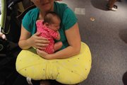 One-week-old Maggie Stultz, above, rests in her mother's  lap. Nursing a baby can be cumbersome, but moms and babies can get a boost with the help of a Boppy, a U-shaped pillow that slips around a mother's  waist and helps support the baby.