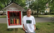 C.J. Brune stands next to a shelf stocked with books in her front yard that anyone can come by and borrow a book from, an endeavor inspired by the Little Free Library project.