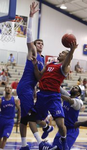 Red team player, Perry Ellis goes up for a bucket against blue team defenders Jeff Withey and Justin Wesley, right, on Wednesday, June 13, 2012 at the Horejsi Center.