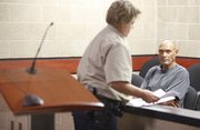 Adolfo Gomez, 52, receives several court documents as he waits for a first appearance Thursday at the Douglas County Jail. Gomez and his wife, Deborah Gomez, 43, are each facing two counts of child abuse and five counts of aggravated endangerment of a child. Adolfo Gomez is also facing one count of felony obstruction. The couple are from Northlake, Ill.