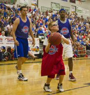Young fan Austin Dixon, in red, looks for a shoot while Ryan Robertson, left, and Aaron Miles watch during the Rock Chalk Roundball Classic held Thursday, June 14, 2012, at Free State High School.