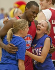 Sarah, right, and Mary Buckels are surprised when Russell Robinson walks up behind them before the start of the Rock Chalk Roundball Classic held Thursday, June 14, 2012, at Free State High.