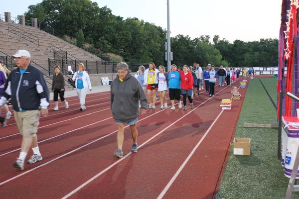Relay For Life of Douglas County participants walk their last lap around the track at Free State High School during the closing ceremony at 5:30 a.m. June 9, 2012.