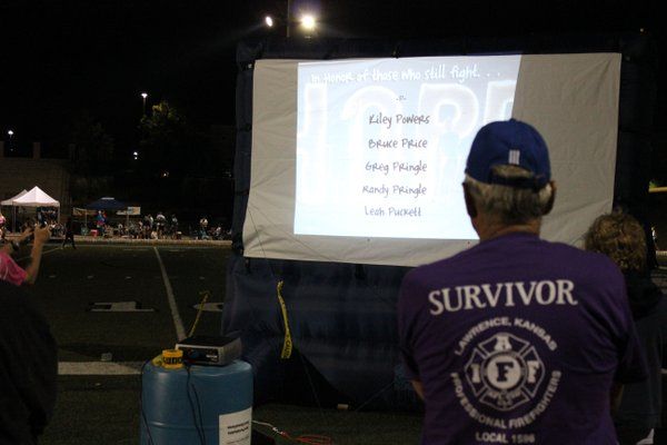 A cancer survivor watches a slideshow that ran during Relay For Life of Douglas County. The slideshow had the names of cancer survivors and those who had lost their lives to cancer as well as those currently fighting the disease. The slideshow ran throughout the night.