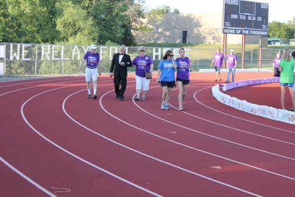 Cancer survivors and their caregivers make their way around the track at Free State High School during Relay For Life of Douglas County.