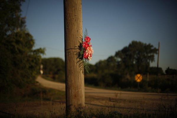 A memorial of flowers are tied to a telephone pole near the entrance to the Lawrence Riverfront Park and also at the train crossing where Ziegler died April 2.