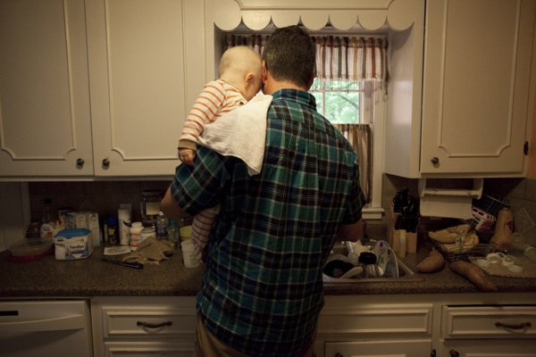 Elliot leans his head against his dad Aaron Polson as he fixes a nighttime bottle on Thursday, June 7, 2012.