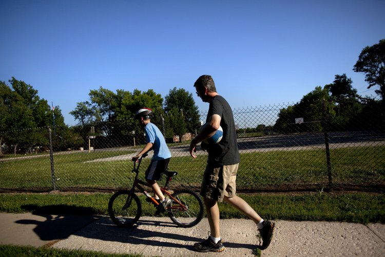 Aaron Polson walks behind his son Owen, 8, who rides his bike to Sunset Hill School to shoot baskets on Monday, June 4, 2012, after dinner. Aaron says that keeping up with and caring for his three sons is helping him through the grieving process.