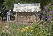 Marilyn Clark had an outdoor oven constructed by area stonemason Keith Middlemas for her backyard patio. The cottage structure includes a wood-fired oven and a built-in slide out grill. Clark says she cooks in it often in the summer because it doesn't heat up the house.