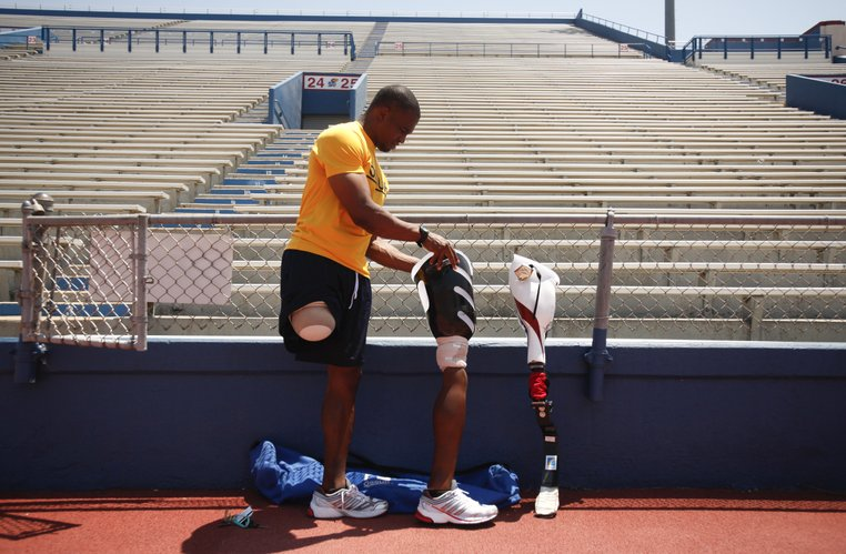 Iraq War veteran and Purple Heart recipient, Kortney Clemons, Lawrence, removes his walking prosthesis as he switches to one designed for running during a day of training to qualify for the upcoming U.S. National Paralympic Championships, Monday, June 18, 2012 at Memorial Stadium. On February 21, 2005, Clemons was inured after an improvised explosive device was detonated forcing his right leg to be amputated. Following his recovery Clemons was inspired to begin running and has