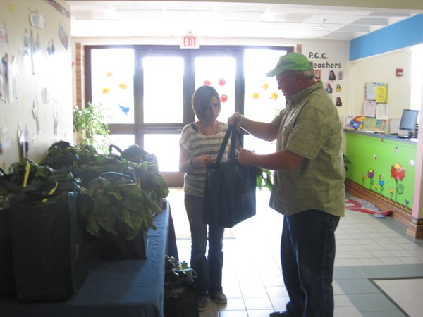 John Pendleton describes the weekly share of produce to a subscriber at Princeton Children's Center