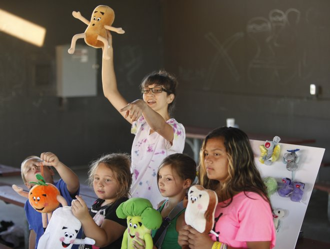 Nutritionist Jessie Danon holds up a stuffed peanut as she asks her students what food group it would fall under during an OrganWise Guys presentation on Friday,  June 22, 2012, at Broken Arrow Park. OrganWise Guys, which is funded through a grant given to Lawrence Parks and Recreation, is a science-based education program to teach kids about nutrition and exercise. Pictured in front are 7-year-old twins, Aidan Schmitz, left, and Lilly Schmitz, Fiona Swaggerty, 9, and Tamika Chanhkhiao, 10.