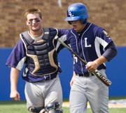 Lawrence Raiders catcher Landon Hay, left, congratulates Aaron Waldeck after Waldeck scored during the Raiders' game against Manhattan Manko on Saturday, June 23, 2012, at Hoglund Ballpark