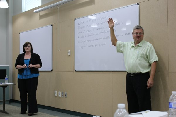 Vickie Collie-Akers, left, of the Kansas University' Work Group for Community Health and Development, counts raised hands as community leaders, including Lawrence-Douglas County Health Department Director Dan Partridge, vote for their top health priorities during a meeting Monday, June 25, 2012, at the Community Health Facility, 200 Maine.