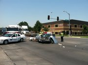 Firefighters help a patient inside a car after an accident near Sixth and Maine streets on Monday, June 25, 2012.