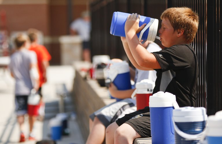 Gabe Setters, 11, Ottawa, takes a gulp from his water jug as he and other youth football campers take a break on Monday morning at Lawrence High School. Temperatures exceeding 100 degrees are expected throughout much of this week.