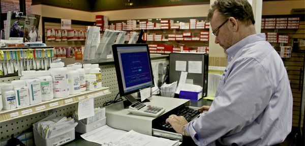 Pharmacist Michael Conlin of Topeka's Jayhawk Pharmacy logs onto the online system for the state's Prescription Monitoring Program, which also still allows reporting using paper forms.  The program allows the tracking of prescriptions that are controlled substances and is intended to safeguard against prescription abuse. The system is relatively new in Kansas but use of it has grown quickly. Future funding for it remains an open question.