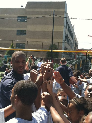 Former Kansas forward Thomas Robinson puts his hand in a break with children during the NBA Fit event near Harlem, New York, on Wednesday, June 27, 2012.