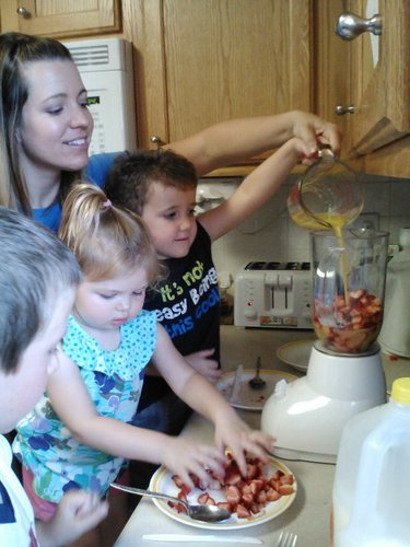 Here the kids all got a turn measuring the orange juice and pouring it into the blender for our Strawberry Lassi recipe.