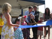 Gov. Sam Brownback and Lt. Gov. Jeff Colyer on Monday cut a ribbon to symbolize a reorganization of two social service agencies. The ceremony took place before more than 100 people outside the Statehouse.