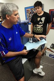 KU debate coach Scott Harris works with Hunter Goh, of Bakersfield, Calif., at KU's Debate Camp in early July. Harris runs several camps every year for high school debaters, in addition to his regular college-level teaching and coaching duties.