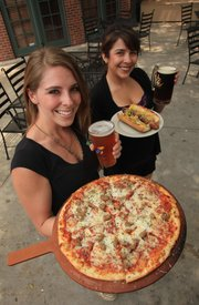 Party in the Park will feature many Lawrence restaurants strutting their stuff. Erica Krause (foreground), holds a pizza and Crimson Phog beer, while DeAnn Young shows off a brat and Wave the Wheat beer, all courtesy of the 23rd Street Brewery.