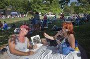 Michael Laing and Jules Richardson, of Lawrence, settle in with a portable fan and a game of cards during the Lawrence Originals Party in the Park Wednesday at Watson Park, Seventh and Kentucky streets. Food was available from Lawrence Originals restaurants with music and children's activities until the evening fireworks display.