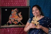 Amrutha Ravikumar, owner of Cosmos Indian Store, holds a statue of the Goddess Dhurga, the goddess of power, which is one of the items available in the new store at 734 Mass.