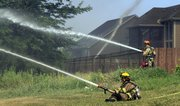 Firefighters work to prevent the spread of a brush and grass fire Thursday morning that threatened Langston Hughes Elementary School and nearby homes on Palisades Drive. The firefighter in the background is wetting down roofs, while the two in the foreground are trying to create a barrier of water between the fire and the homes.