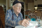 Gene Ward rifles through the numerous books and written histories he has of the 449th Bombardment Group in World War II, wearing a hat emblazoned with the group's symbol. He has attended three of the group's reunions.
