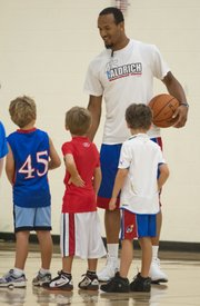 Kansas senior guard Travis Releford chats with some of the smaller participants of the Cole Aldrich basketball camp Monday, July 9, 2012, at Olathe Northwest High School.