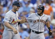 All-Star MVP Melky Cabrera, right, of the San Francisco Giants, celebrates his two-run, fourth-inning home run with the Cardinals' Matt Holliday. Cabrera helped the NL to an 8-0 rout of the AL in the All-Star game on Tuesday, July 10, 2012, in Kansas City, Mo.