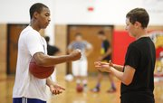 Lawrence High senior Sterling Fuller, left, loses a match of rock-paper-scissors to freshman Parker Kirkpatrick, as the two determine which team gets the ball prior to a game of three-on-three on Wednesday, July 11, 2012, at LHS.