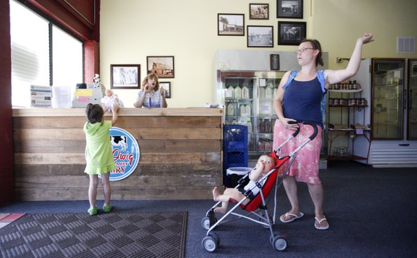 Lawrence mother Alisha Swanson engages in an animated conversation with Laurel Iwig Monday at the Lawrence Iwig Family Dairy store, 1901 Mass. Iwig and her husband Tim opened the market in February, in which they are selling their dairy products as well as produce, meats and other products from local producers. Also pictured are two of Swanson's children, Mackenna, 4, and Sam, 11 months.
