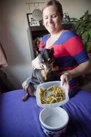 Amy Long feeds her dog Minnie green beans for a snack. Long adopted Minnie from the Lawrence Humane Society, 1805 E. 19th St., three years ago. Minnie was overweight then, but with good portion control and healthy snacking, the miniature pincer went from 22 pounds to 15 pounds.