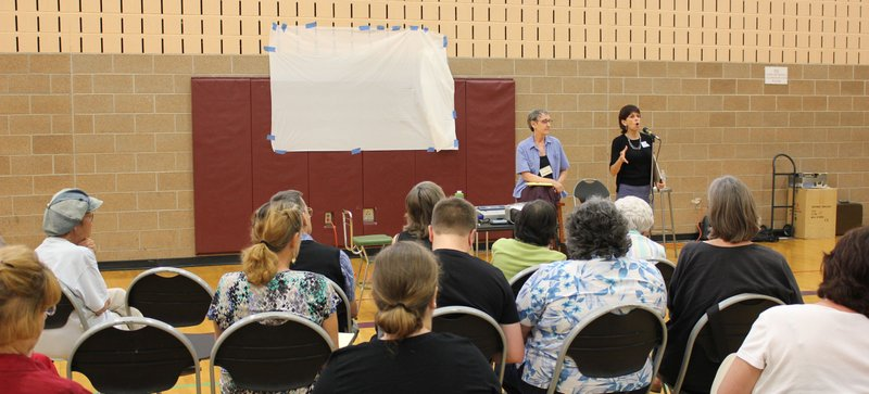 In front, Lawrence resident Bonnie Uffman, left, and Judy Willett, of Village to Village Network, answer questions during a community meeting about starting a village for older adults in Lawrence. About 70 people attended the meeting Thursday, July 12, 2012, in the East Lawrence Recreation Center.