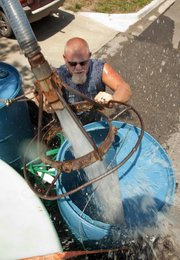 PETE GOANS, OF BALDWIN CITY, fills his water tanks Wednesday. Goans buys 500 gallons from the city of Lawrence daily to water his fields. 