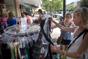 Suzie Craig, right, Lawrence, and her daughter Anna, a junior at Free State high school, check out a rack of clothes at Britches during the annual Downtown Lawrence Sidewalk Sale, Thursday, July 19, 2012.