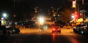 Only streetlights and car lights illuminate the way for early morning shoppers as they start a day of shopping at the annual Downtown Lawrence Sidewalk Sale, Thursday, July 19, 2012.
