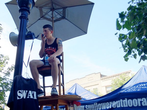 Sunflower Outdoor and Bike mechanic Willie Stein announces deals from atop a makeshift lifeguard chair outside the bike shop during the Downtown Lawrence Sidewalk Sale.