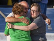 "Tom Sullivan, center, embraces family members outside Gateway High School where he has been searching franticly for his son Alex Sullivan who celebrated his 27th birthday by going to see ""The Dark Knight Rises,"" movie where a gunman opened fire Friday, July 20, 2012, in Aurora, Colo."