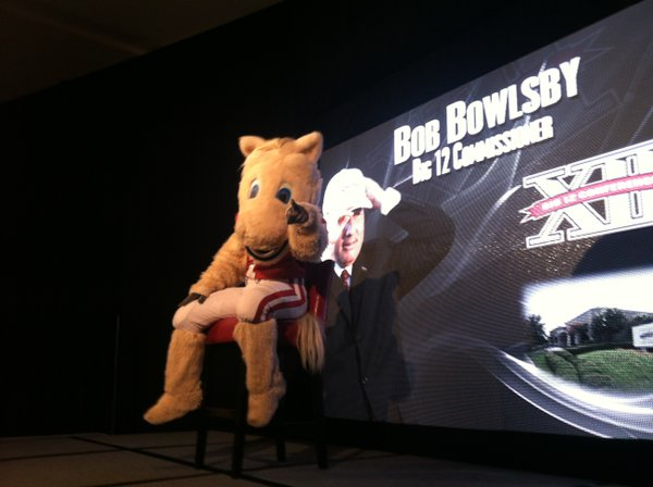 """Boomer"" the Oklahoma mascot sits in the place of Big 12 commissioner Bob Bowlsby before the start of Big 12 football media days on Monday, July 23, 2012, in Dallas."