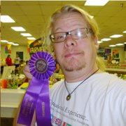 Harold Agnew, Lawrence, displays the champion ribbon his basil and chive bagels won at the 2011 Douglas County Fair open baking contest.